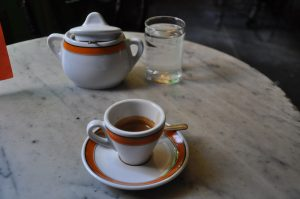 An espresso on a marble table, with a glass of water and a sugar bowl in the background