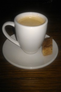 A generic mug of coffee, on a saucer, with a biscotti to one side