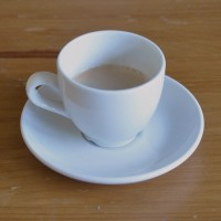 An espresso, in a classic white cup on a white saucer on a table