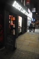 Brick Lane Coffee from the outside after dark, with the famous A board (being uncontroversial for once)