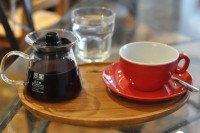 A carafe of coffee and a bright red cup from Coffee Aroma, Lincoln.