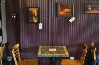 One of the many fine tables in True Grounds, with some of Maria Marx's paintings hanging on the wall above it.