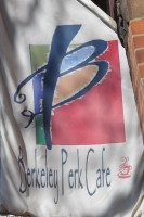 The Berkeley Perk Cafe logo on a flag hanging outside the shop