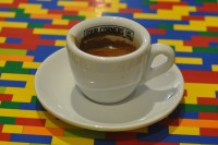 An espresso from Four Corners Cafe in a white cup with Four Corners Cafe Limited written on the inside of the rim