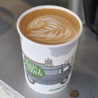 A latte, complete with latte art by Rory, in a Bean About Town takeaway cup from the Kentish Town cart.