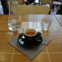 A very fine espresso in a hard to photograph black cup from Coutume, complete with carafe of water.