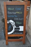An A-board outside Ground Coffee, Hove saying Hello, Bonjour, Ciao, Hallo, Guten Tag, Dia Duit, Hola, G'Day