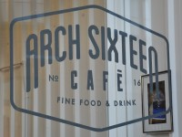 The Arch Sixteen Logo in the window of Arch Sixteen Cafe: Fine Food & Drink