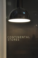 One of the Continental Stores black light fittings hanging above the name written in white on a darkened window.