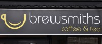 The Brewsmiths logo, a smiling yellow cup next to the words 'brewsmiths coffee & tea'