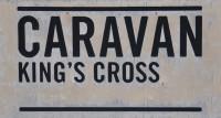 "The Caravan King's Cross Sign: ""Caravan King's Cross"" in black letters on a white background"