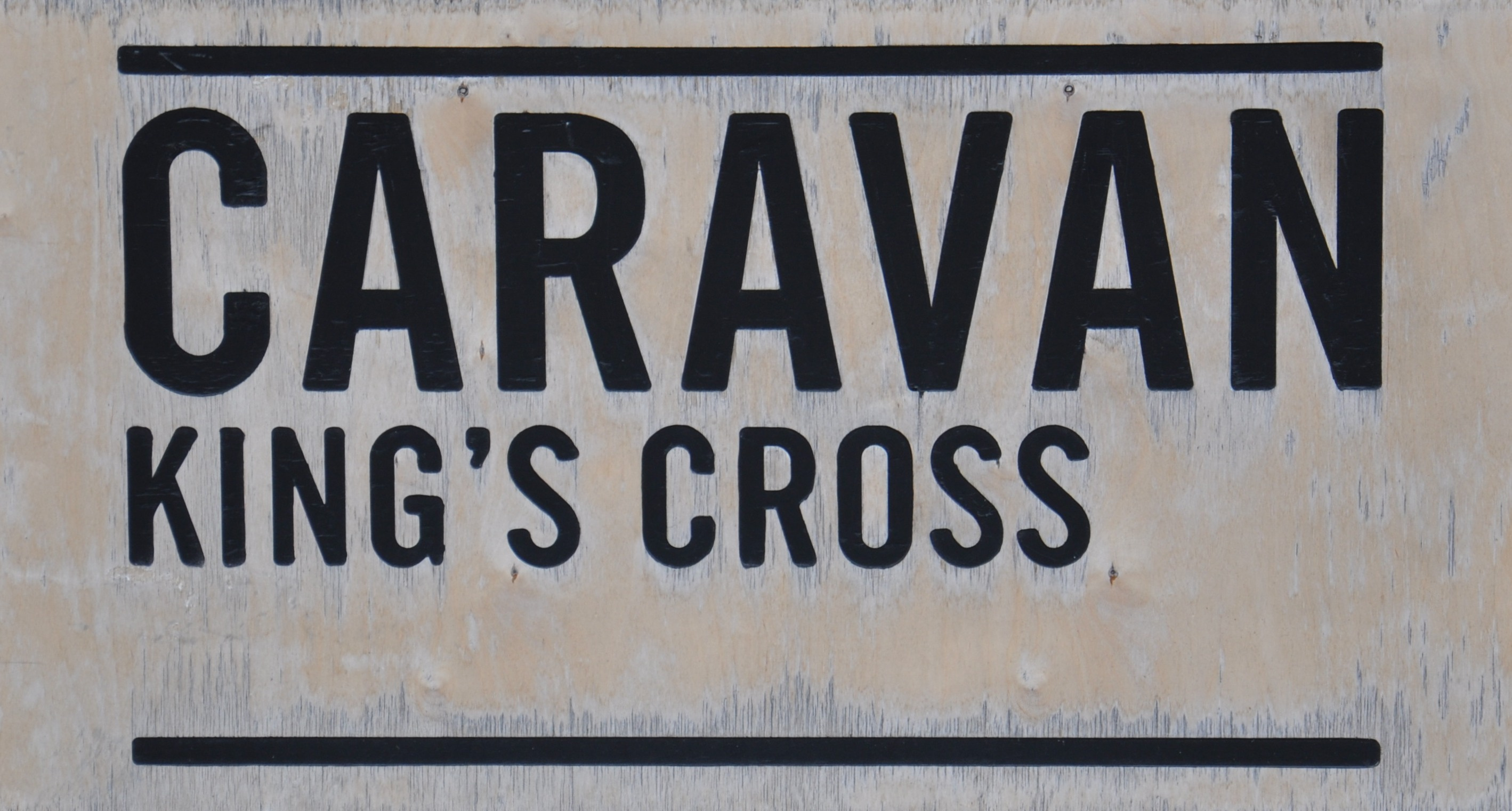 "The Caravan King's Cross Sign: ""Caravan King's Cross"" in black letters on a white background"