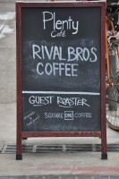 The A-board outside Plenty in Rittenhouse, proudly displaying its coffee credentials with local roasters Rival Brothers and Square One Coffee