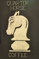 The Quarter Horse Coffee Logo, a style white chess piece (a knight) against a black background