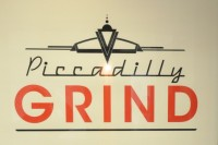 The Piccadilly Grind sign painted on the back wall above the bench.