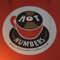 The Hot Numbers logo: a red espresso cup on a saucer drawn to look like a vinyl record. The surface of the coffee in the cup is also a vinyl record.
