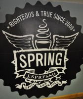 "The Spring Espresso logo: a winged espresso cup with the slogans ""Righteous & True Since 2006"" above and ""Spin and Roll"" below."