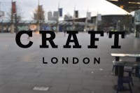 "The word ""CRAFT"" written above the word ""LONDON"" in the window of CRAFT London, the O2 Arena in the background."
