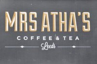 "The Mrs Atha's Logo: the words ""Mrs Atha's"" in gold capitals, with the words ""Coffee & Tea"" written beneath, all above the word ""Leeds"" written in script."
