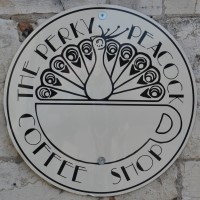 "The Perky Peacock logo, a black-and-white roundel with a stylised peacock in the top half and the words ""The Perky Peacock Coffee Shop"" written around the edge."