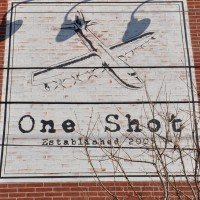 The One Shot logo, an eight-engined, propeller-driven flying boat, painted on the side of the wall of One Shot.