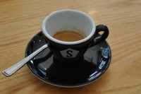 An espresso, part of a split shot, at Strangers Coffee House, in a classic black tulip cup.