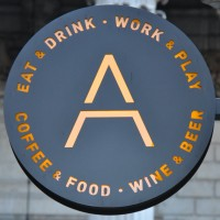 "The Artigiano Espresso Logo, a capital A in gold on a slate-grey circle, with the words ""Eat & Drink * Work & Play * Coffee & Food * Wine & Beer"" written around the edge."