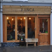The store front of Finca on Great Western Road, Dorchester, the bulbs inside glowing in the fading evening light.
