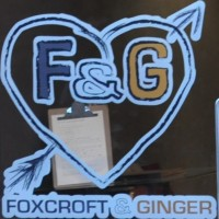 "The letters ""F & G"" enclosed in a heart with an arrow through it, painted on the door, with Foxcroft & Ginger written underneath"