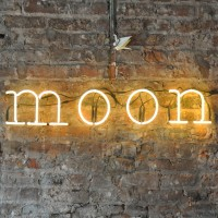 "A neon sign, ""moon"" on the bare brick chimney breast of Moon Beer & Coffee in Chester"