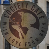 The Society Café sign, hanging outside in Kingsmead Square. It shows a lady in silhouette, about to drink from a cup of coffee.
