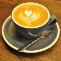 A flat white from Bluestone Lane in a classic grey cup, with tulip motif latte art.