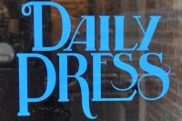 "From the window of Daily Press Coffee: the words ""Daily Press"" written in blue in serif capitals."