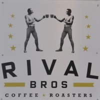 Two bare-chested men, dressed as old-fashioned pugilists, but each holding a large coffee cup in their hands.