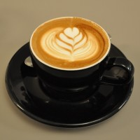 A flat white in a classic black cup at the Electric Coffee Company in Ealing.