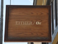 The sign hanging outside Either/Or in Portland. The words EITHER/Or on a wooden board.