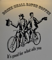 "The Small Batch Logo: two gentlemen on a tandem, one holding a coffee pot, the other a mug. Above is written ""DRINK SMALL BATCH COFFEE"" and below ""It's good for what ails you""."