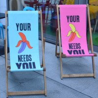 "A pair of multi-coloured, Beany Green banana-themed deckchairs. Each bears the slogan ""Your banana needs you"" although the word banana is replaced with the picture of a partially-peeled banana."