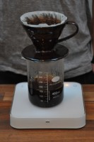 A V60 at Foundry Coffee Roasters, standing on a glass beaker half full of coffee, all on a set of scales.