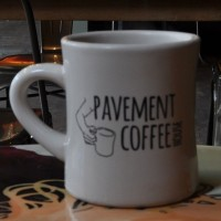 "A plain white mug with the words ""Pavement Coffeehouse"" in black, The logo is completed by a drawing of an arm and hand holding a coffee mug, the arm bent to mimic the curve of the mug's handle."