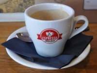 A classic white tulip espresso cup with the Espresso Kitchen logo on the front