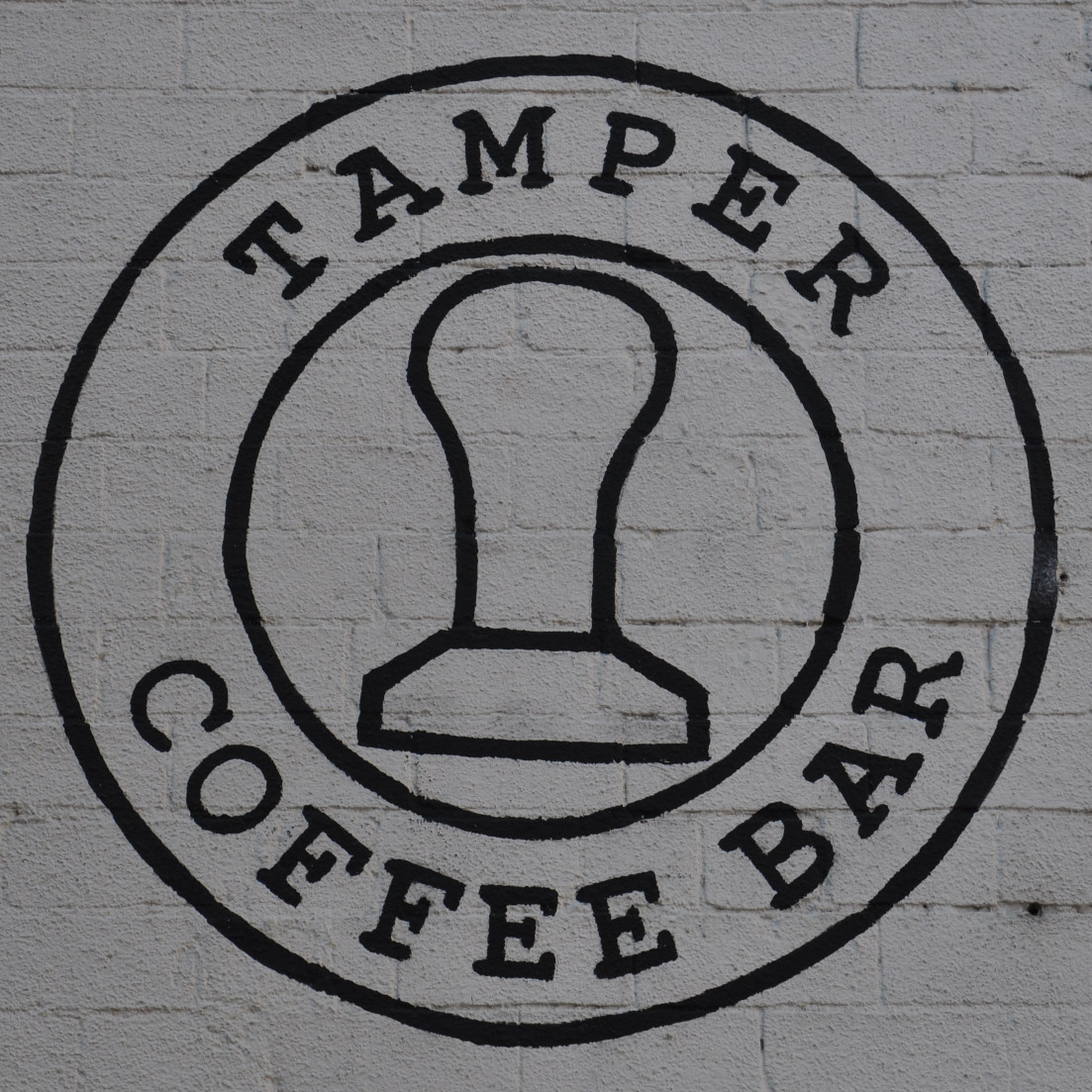 "The Tamper Coffee logo painted in black on the whitewashed side of Sellers Wheel. The words ""Tamper Coffee Bar"" written in a ring around the outline of tamper."