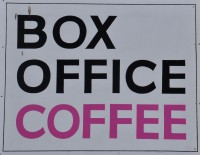 "The sign from the window of Box Office Coffee, Bridport.: the words ""Box Office Coffee"" in capitals, one word per line. The word ""coffee"" is in pink."