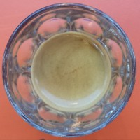 An espresso in a glass, seen from directly above. The coffee is a single-origin Papua New Guinea bean, served in Jonestown Coffee, Bethnal Green Road.