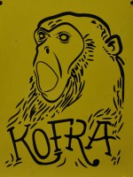 The Kofra logo, an ape's head, mouth wide open, drawn in black on a yellow background, the words Kofra underneath.