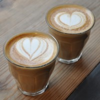 Two flat whites, in glasses, with heart pattern latte-art, at The Little Red Roaster, St Andrews Hill, Norwich.
