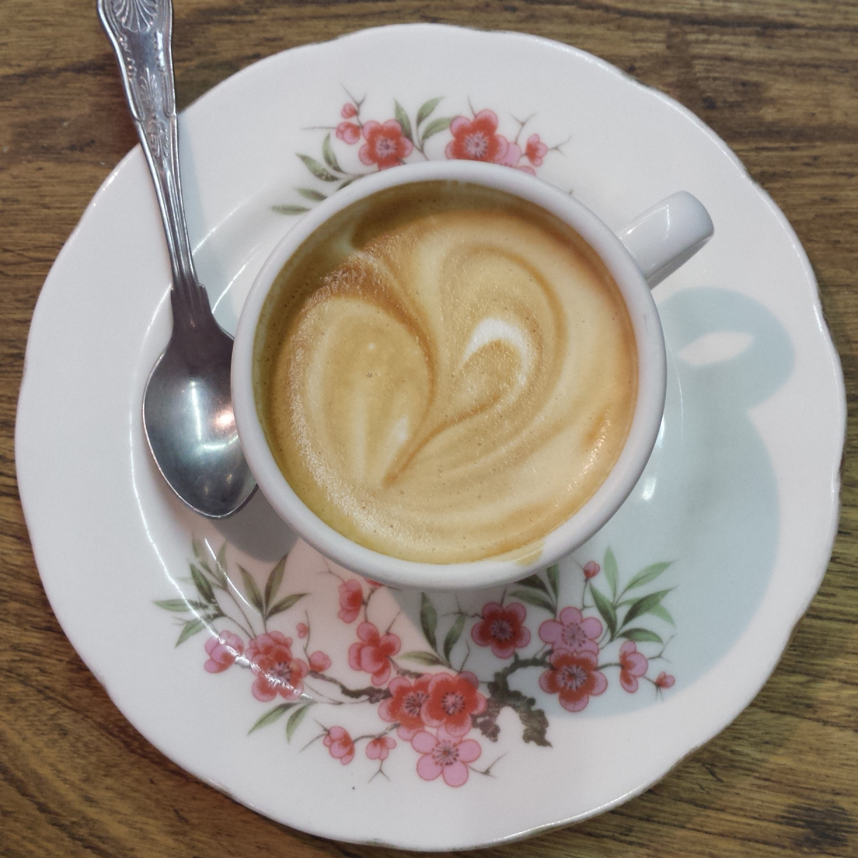 A lovely, creamy piccolo in a classic espresso cup, seen from above on an over-sized floral saucer.