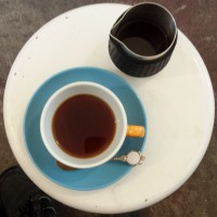 A cup of filter coffee, seen from above, next to a handleless jug, on a white, round table at Filament Coffee.