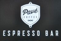 "The sign above the door at Pavé Coffee: the words ""Pavé Coffee"" in black on white shield on a black background, with the words ""Espresso Bar"" underneath in white capitals."