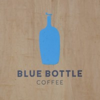 "The Blue Bottle Coffee logo from the A-board outside the Chelsea coffee shop: the outline of a bottle painted in solid blue above the words ""Blue Bottle Coffee""."